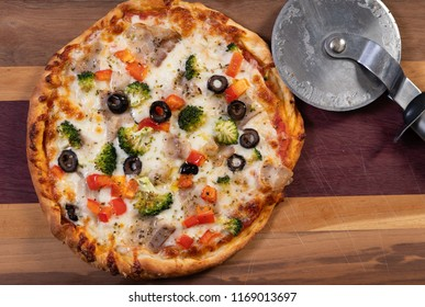 Delicious homemade personal pan pizza with red peppers, black olives, broccoii and bacon ready to eat