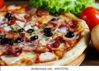 Delicious homemade pizza with mozzarella, ham, olives and fennel. Wooden background, selective focus.