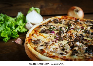 Delicious homemade pizza with mozzarella, mushrooms, beef and chicken. Wooden background, selective focus.