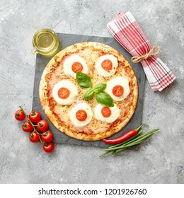 Delicious homemade pizza with tomatoes, mozzarella and basil. Top view with copy space on gray stone table.