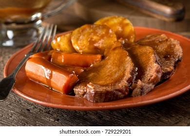 A delicious homemade pot roast dinner with potatoes, carrots, and gravy.
