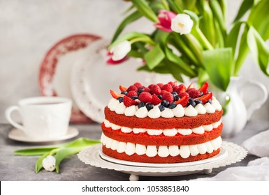 Delicious homemade red velvet cake decorated with cream and fresh berries