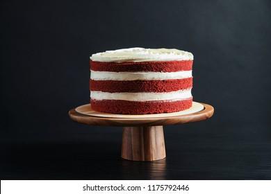 Delicious homemade red velvet cake on wooden stand against black background