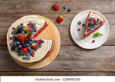 Delicious homemade red velvet cake with fresh berries on wooden table, top view