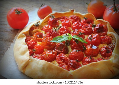 Delicious homemade rustic open pie or galette with tomato, cheese on wooden background. Top view .