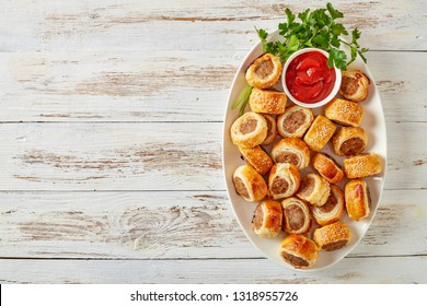 Delicious homemade sausage rolls on a white oval platter with tomato sauce on a wooden rustic table, finger food, english cuisine, view from above, flatlay, copy space