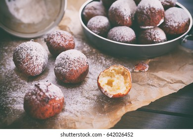 Delicious homemade sour cream ball doughnuts powdered with sugar, on dark wooden background, close up. Toned picture