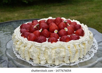 Delicious homemade strawberry cake on a table in a garden