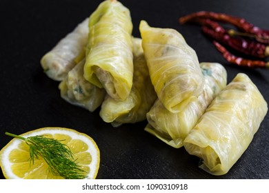 Delicious homemade stuffed cabbage leaves (the traditional dolma of the mediterranean cuisine) on black dish with dill, red pepper and lemon
