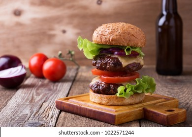 Delicious homemade two patty burger with lettuce, cheese. tomato, red onion and tomato sauce