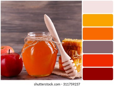 Delicious honey with apple on table and palette of colors
