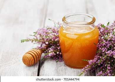 Delicious honey in pot or jar and flowers heather on wooden vintage table.