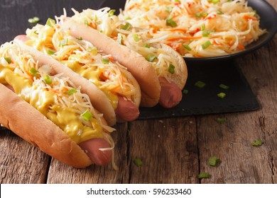 Delicious hot dog with sausage, sour cabbage and mustard close-up on the table. Horizontal