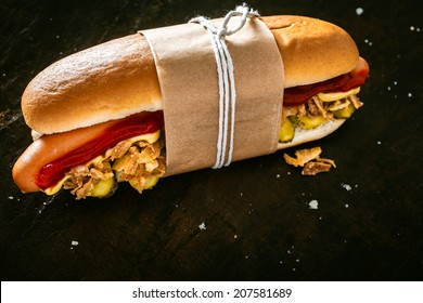 Delicious hot dog with a smoked Vienna sausage and salad ingredients with tomato sauce and mustard tied in a brown wrapper against a dark background