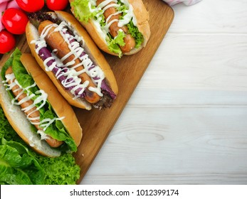 Delicious hot dogs served on wooden board. Selective focus. Empty space for text.
