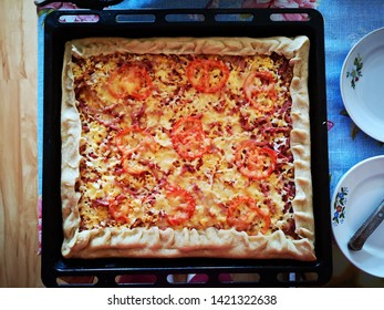Delicious, hot, freshly prepared homemade pizza with cheese and tomatoes on a baking sheet with beautiful round plates and a knife. Homemade food. Cooking at home.