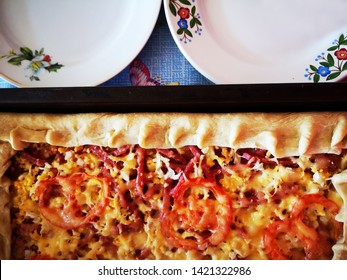 Delicious, hot, freshly prepared homemade pizza with cheese and tomatoes on a baking sheet with beautiful round plates. Homemade food. Cook at home.