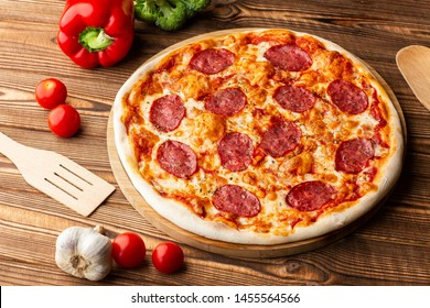 Delicious hot homemade Pepperoni pizza on the wooden table. Pepperoni Pizza - Fresh homemade pizza with pepperoni, cheese and tomato sauce on rustic black stone background with copy space.