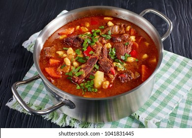 delicious hot hungarian goulash with beef meat, paprika, vegetables and csipetke - small egg pasta in stainless steel pot on black wooden table, classic recipe, view from above, close-up