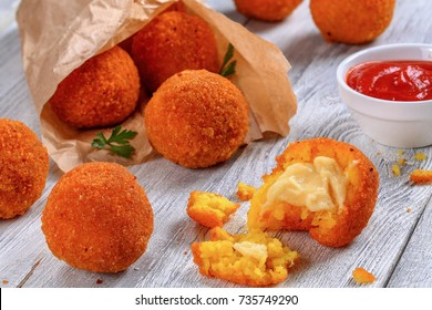delicious hot italian arancini - saffron rice balls stuffed with cheese in paper bag on old wooden table with tomato sauce on background,  view from above, close-up