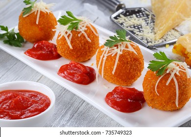 delicious hot italian arancini - saffron rice balls stuffed with melted cheese  topped with grated parmesan cheese and parsley on rectangular plate with tomato sauce  view from above, close-up