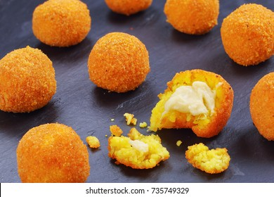 delicious hot italian arancini - saffron rice balls stuffed with melted cheese on black slate tray,  view from above, close-up