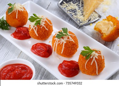 delicious hot italian arancini - saffron rice balls stuffed with melted cheese  topped with grated parmesan cheese and parsley on rectangular plate with tomato sauce  view from above