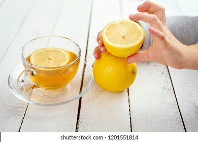 delicious hot tea with honey and child's hand with lemons on an old white wooden table