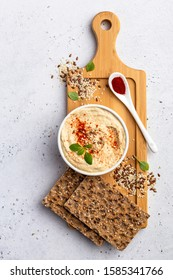 Delicious hummus garnished with seeds, ground spices and herbs