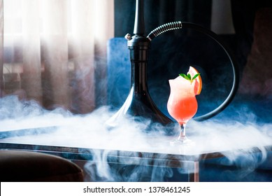 Delicious icy grapefruit coctail with shisha smoke on the background