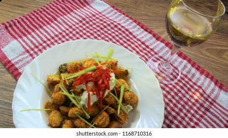 Delicious and interesting food, sweet potatoes yams balls baked in the oven on the high temperature with spices and herbs on the red and white background and wooden table with the glass of white wine