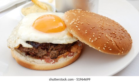 delicious isolated american burger with prepared egg with sauce and fries served on table