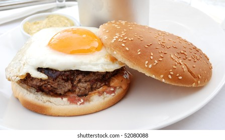 delicious isolated american burger with prepared egg on table