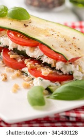 Delicious Italian appetizer of tomato, zucchini slices, nuts, basil and fresh cheese.