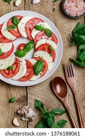 Delicious italian caprese salad with ripe tomatoes, fresh basil and mozzarella cheese on wooden rustic background. Italian caprese salad in white plate with sliced tomatoes.