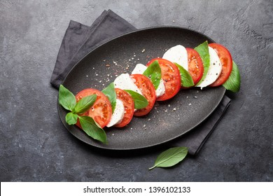 Delicious italian caprese salad with ripe tomatoes, fresh garden basil and mozzarella cheese. Top view flat lay