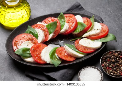 Delicious italian caprese salad with ripe tomatoes, fresh garden basil and mozzarella cheese