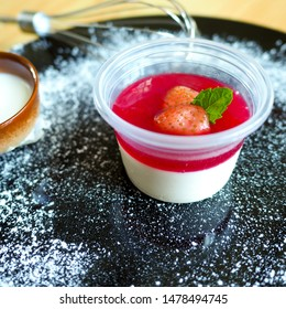 Delicious Italian dessert panna cotta with berry sauce, fresh strawberry and mint