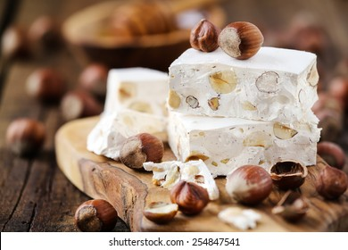 Delicious Italian festive torrone or nougat with hazelnuts on a wood