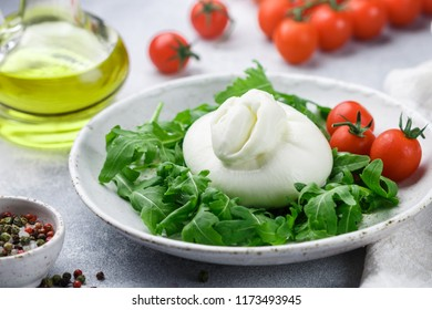 Delicious Italian fresh burrata cheese with arugula salad, cherry tomatoes and olive oil in a white plate. Gourmet snack. Selective focus