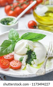 Delicious Italian fresh burrata cheese with cherry tomatoes, Basil pesto and olive oil in a white plate. Gourmet snack. Selective focus