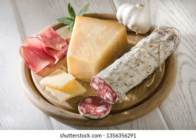 Delicious Italian Mediterranean Antipasti Plate With Hard Cheese, Parmesan, Grana Padano, Parma Ham, And Air-Dried Salami On A Rustic Wooden Board Top View