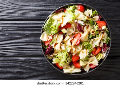 Delicious Italian pasta salad with avocado, strawberries, lettuce, dressed with balsamic sauce close-up on a plate on the table. horizontal top view from above