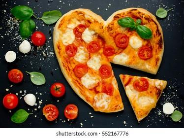 Delicious Italian pizza with cherry tomatoes, mozzarella and basil shaped heart