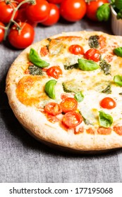 Delicious italian pizza on tablecloth with tomatoes