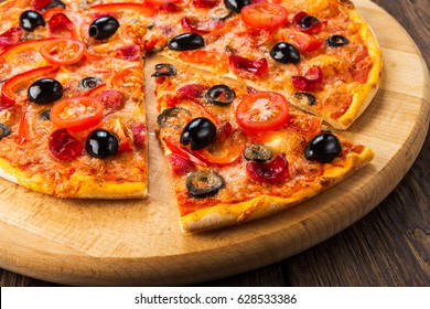 Delicious italian pizza with salami pepperoni, cherry tomatoes and black olives - thin pastry crust at wooden table background