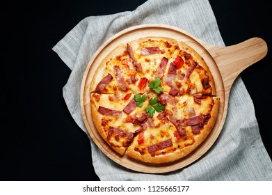 Delicious Italian pizza sliced ham, bacon and cheese with food ingredients on old kitchen table.