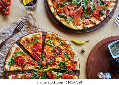 Delicious italian pizzas served on wooden table with ingredients shot from above