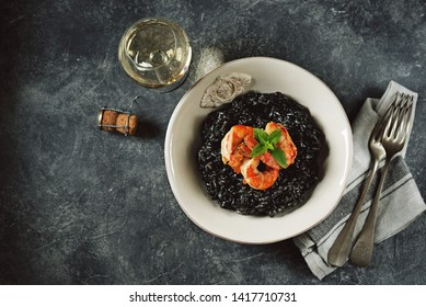 Delicious Italian risotto with grilled big tails of shrimp and cuttlefish ink (squid-ink). Black risotto. Healthy tasty food.  Top view. Copy space.