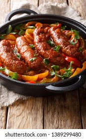 Delicious Italian sausages grilled with bell peppers, onions and tomatoes close-up in a frying pan on the table. vertical